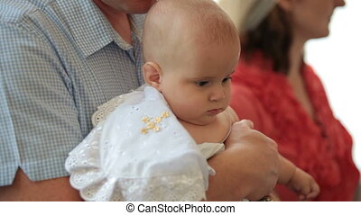 Father holding baby at christening in church