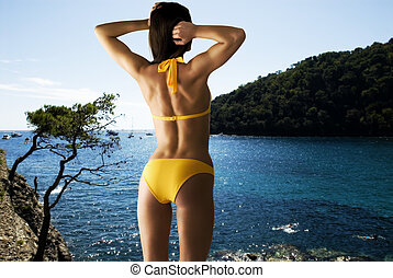 sea time - young woman near the sea with showing her tonic...