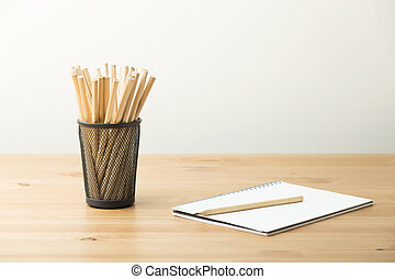 Pencil in pot with notebook