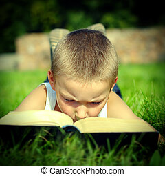 Child reads a Book - Toned photo of Kid attentively reads...