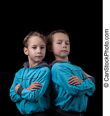 Portrait of adorable twin boys isolated on black background