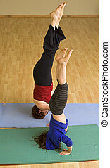 grandmother and child exercising doing a headstand together