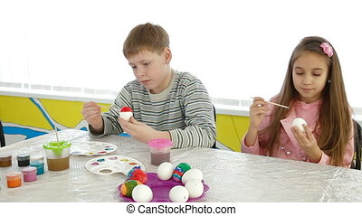 Children painting easter eggs