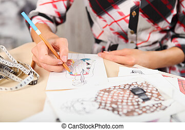 Dressmaker is drawing a fashion sketch. Close up of the...