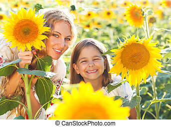 Happy mother and her little daughter in the sunflower field....