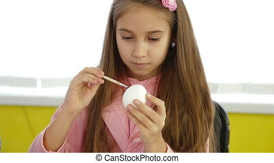 Little girl painting easter egg