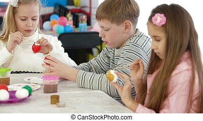 Children decorating easter eggs