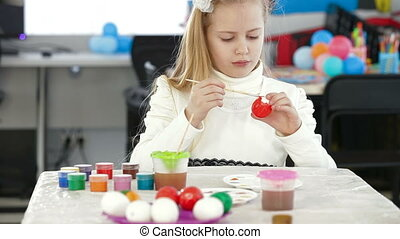 Cute girl painting easter eggs