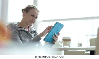 Woman in cafe using her touchpad