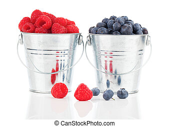 blueberry and raspberries berries in a metal bucket,...