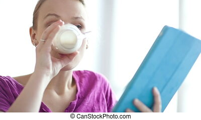 Woman using her touchpad - Young woman using her touchpad...