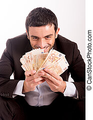 Happy business man sitting on piggy bank counting money...
