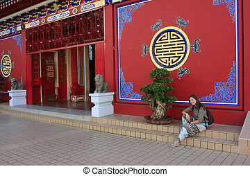 Tourist resting on the stair of Chinese buddhist temple,...