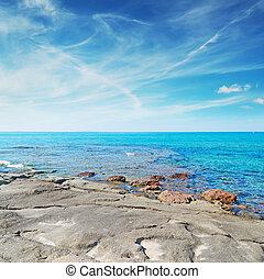 grey rocks in Lu Bagnu - Lu Bagnu rocky shore on a cloudy...