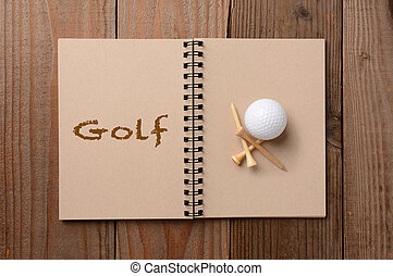 Golf Ball and Tees on Open Notebook