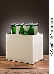 Six Pack Beer on Wood Table - Closeup of a six pack of green...