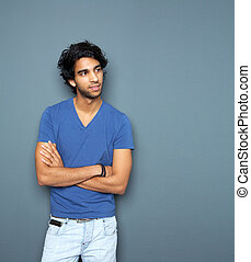 Portrait of a casual man standing with arms crossed against...