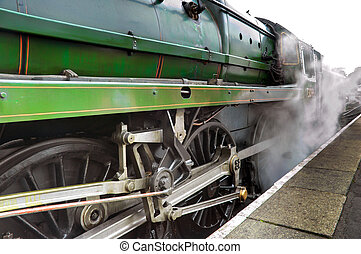 Releasing Steam - Old steam train engine releasing steam at...