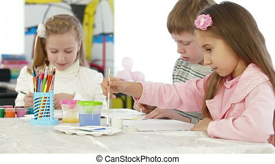 three kids painting in watercolor - Children are painting in...