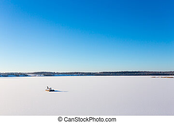 Frozen lake with ice and snow, sunny winter day. Forest