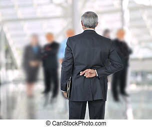 Standing Businessman with fingers crossed behind back He is...