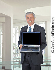 Smiling Middle aged Businessman with Computer - Smiling...