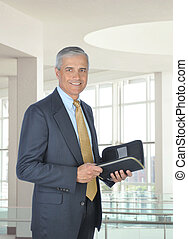 Smiling Middle aged Businessman with Planner - Smiling...