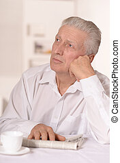 Senior man with newspaper aat home sitting at table