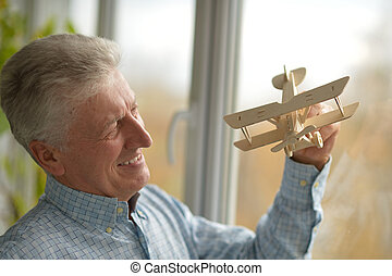 Senior man with wooden plane at home