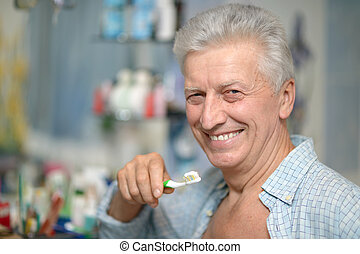 Man is brushing his teeth - Cute aged man is brushing his...