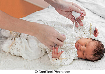 Dressing up a baby - Hands of mother which dresses her baby...