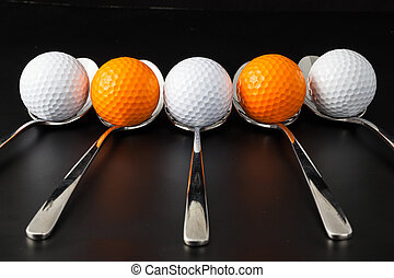 Spoons and golf balls - Spoons and different golf balls on a...