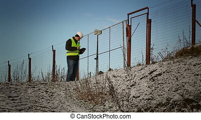 Worker with tablet PC near to fence episode 6