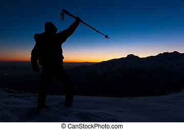 At sunset a man stands on a snowy peak expressing his joy for have reached the top of a mountain peak. Concept: adventure, achievement, sport.