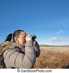birdwatching - woman with binoculars birdwatching, copy...