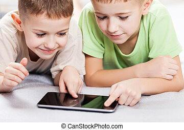 Two little smiling child boy brothers playing games or...