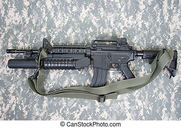 M4A1 carbine equipped with an M203 grenade launcher on ACU...