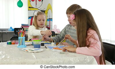 Children painting and playing at kindergarten