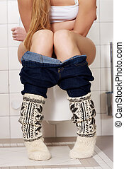 Young caucasian woman is sitting on the toilet. urinary...