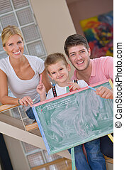 family drawing on school board at home - happy young family...