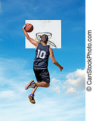 one-handed dunk - basketball player dunking with a sky in...