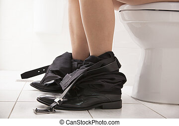 Close-up view of  business male sitting on the toilet seat