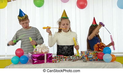 Children blowing bubbles at birthday party