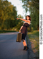 roadside - young woman waitin a car from the roadside