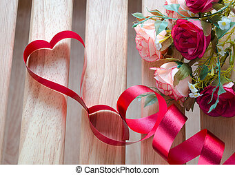 Red satin ribbon heart with artificial rose flowers