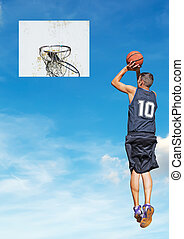 shooting in the sky - basketball player shooting with the...