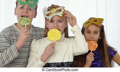 Children having fun at birthday party with party masks and...
