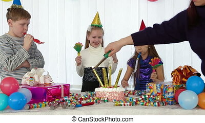 Lighting candles on the cake at kids birthday party