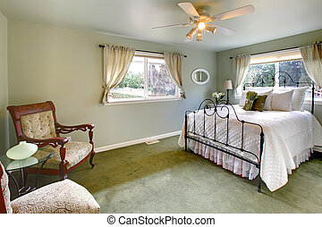Olive tones bedroom with antique iron frame bed