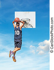 two-handed dunk - basketball player dunking with a sky in...